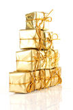 Gold gift rapped parcel pyramid. On white background royalty free stock photo