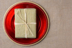 Gold Gift on Red Charger Stock Image