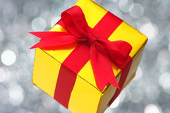 Gold gift on silver blurry lights background. Royalty Free Stock Photos