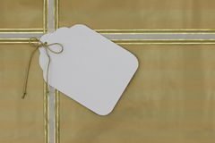 Gold gift wrapped package with large blank tag Stock Image