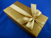 Gold gift. A gift wrapped up in gold royalty free stock photos