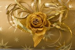 Gold gift wrapping. Gold flower and ribbons gift wrapping stock photos