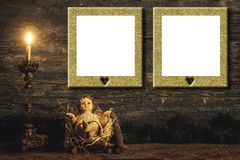 Gold frames with Christmas statuary. Gold gilt frames with white copy space over statuary of baby Jesus and candle on rustic wood Royalty Free Stock Photos