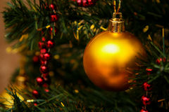 Gold glass bauble and red garland Stock Image