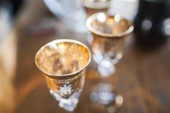 Gold glasses in the defocus on a wooden table.  Royalty Free Stock Photos