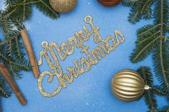 A gold gleaming Merry Christmas inscription on a blue background. A gold gleaming Merry Christmas inscription with spruce branches, cinnamon sticks and gold Royalty Free Stock Photography