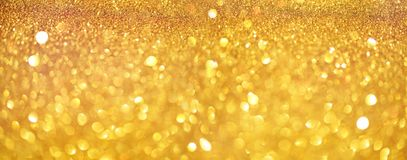 Gold glitter banner. Shiny abstract textured background with golden lights, bokeh. Christmas, new year concept with copy space for stock image