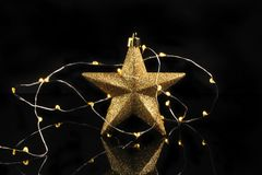 Star and lights. Gold glitter Christmas star with fairy lights against a black background stock photo