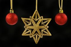 Gold glitter Christmas star and red baubles. Gold glitter Christmas star and red glitter baubles against a black background Stock Photography