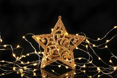 Glitter star and lights. Gold glitter Christmas star surrounded by fairy lights against a black background royalty free stock image