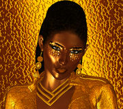 Close up fashion eye shadow and face of woman. Gold glitter eye shadow with unique hair style and gold background. Send a Powerful fashion message with our Royalty Free Stock Photos