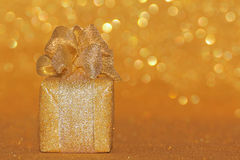 Gold christmas  glitter gift box present. Golden gift box, present   wrapped in golden glitter paper with golden ribbon. Golden abstract defocused background Stock Photos