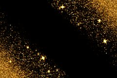 Gold glitter with glowing sparks on black background. Defocused gold glitter with glowing sparks lights on a black background. Holiday greeting card Stock Images