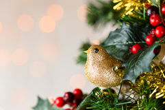 Gold glitter robin on Christmas tree. Copy space. Royalty Free Stock Photo