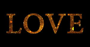 Gold glitter sparkle particles love word shape on black background, holiday festive valentine day love stock video footage