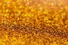 Gold Glitter Stars Glow Background. Sparkling gold glitter, stars and bokeh blur background, wallpaper Stock Images