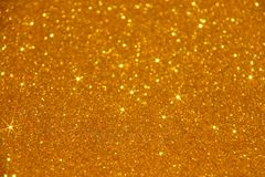 Gold Glitter Stars Sparkle Background - Stock Photo. Gold glitter stars sparkle background : golden wallpaper in blurred lights stock image