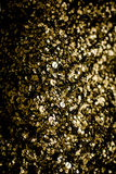 Gold glitter texture isolated on black square. Amber particles c Stock Images