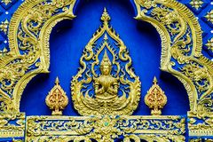 Gold god convex art with blue background. Gold god convex art raise up his hand, with blue background and Thai gold pattern decorate around royalty free stock images