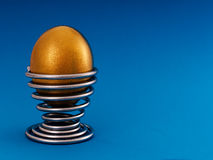 Gold, golden egg in eggcup - nest egg, investment concept Stock Photos