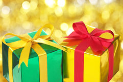 Gold and green gifts on blurry lights background. Stock Photos