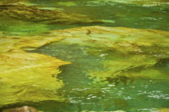 Gold and Green texture of rocks and underwater landscape. Rocky landscape underwater with emerald green water in textured pattern royalty free stock photos