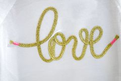 The gold hand craft text Love typo knitting on the white textile royalty free stock photos