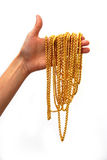 Gold in hand. Many golden necklaces in hand stock photography