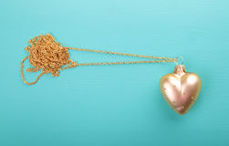 Gold heart with gold chain.  royalty free stock photos