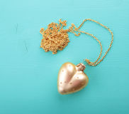 Gold heart with gold chain.  stock photos