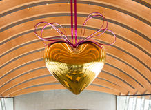 Gold heart hanging with purple metal ribbon Stock Photo