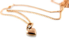Gold heart pendant with chain. On white background stock photography