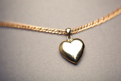 Gold heart pendant. On warm background royalty free stock photos