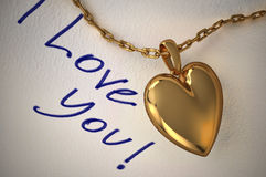 Gold heart pendant on white paper with the inscription I love you, handwritten on it. Royalty Free Stock Photo