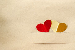 Gold heart and red heart on vintage brown paper. Gold heart and red heart on vintage brown paper background with copy space stock image