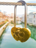Gold heart shaped padlock hanging from string. Crossing bridge of river Stock Photography