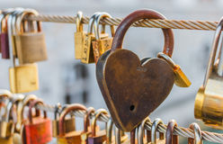 Gold heart shaped padlock hanging from string. Crossing bridge of river Stock Images