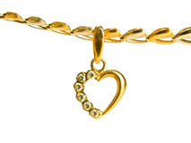 Gold heart-shaped pendant. Female golden decoration on white background Royalty Free Stock Photo