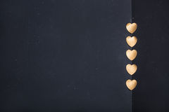 Gold heart stickers on dark texture background Royalty Free Stock Photo