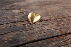 Gold heart for Valentines Day concept on wooden background stock images
