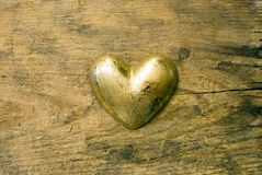 Gold heart on wood Royalty Free Stock Image