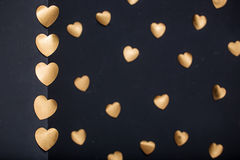 Gold hearts stickers on dark  background Stock Image