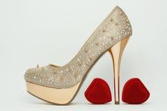 Gold high-heeled shoe. Stock Photo