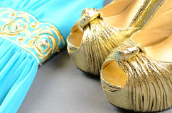 Gold high-heeled shoes, clutch bag and blue dress with gold  acc Royalty Free Stock Photo