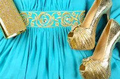Gold high-heeled shoes, clutch bag and blue dress with gold acce Stock Image