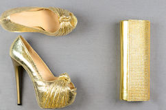 Gold high-heeled shoes and a clutch bag on a gray background Stock Photo