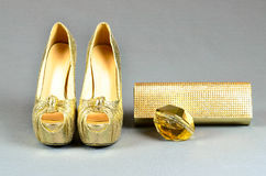 Gold high-heeled shoes, clutch bag and perfume on a gray  backgr Stock Images