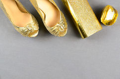 Gold high-heeled shoes, clutch bag and perfume on a gray backgro Royalty Free Stock Image