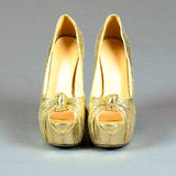 Gold high-heeled shoes on a gray  background Royalty Free Stock Images