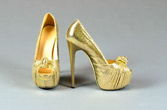 Gold high-heeled shoes on  a gray background Royalty Free Stock Photography